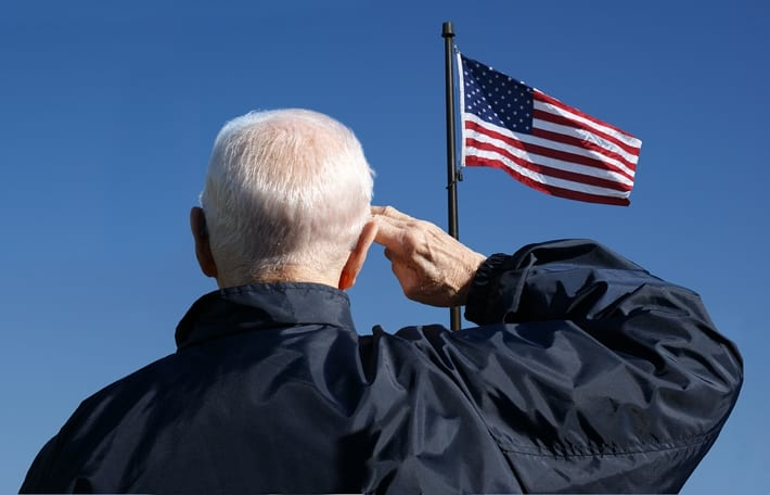 Older man saluting to American flag
