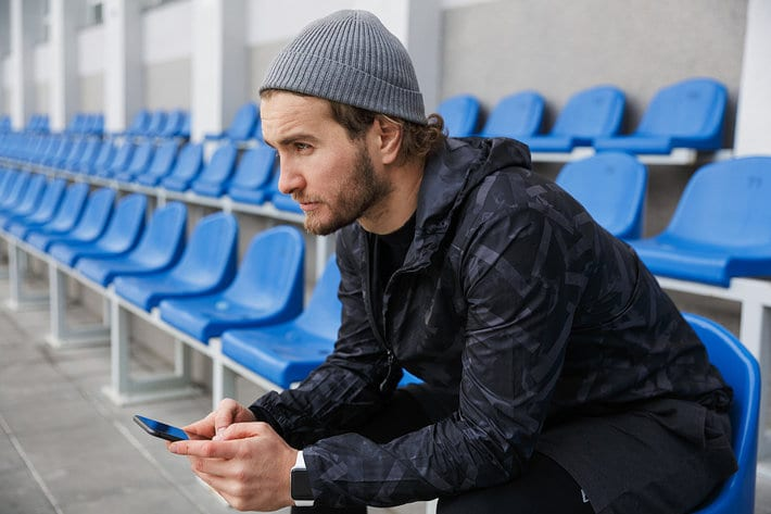 Man Using Phone at Football Stadium